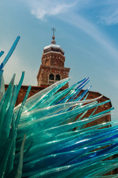 detail of blue murano glass sculpture in murano with san giacomo church in background, venice - italy - glasskulpturen stock-fotos und bilder