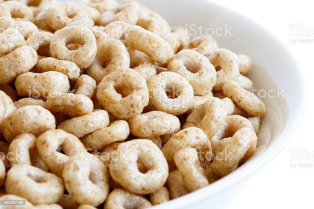 Detail of bowl of honey cheerios on white. stock photo