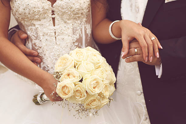 Detail of bride's roses bouquet and hands holding stok fotoğrafı