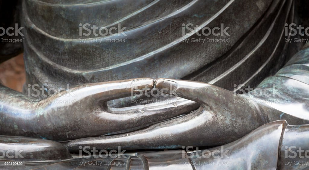 Detail of Buddha statue with Dhyana hand position, the gesture of meditation stock photo