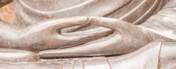 Detail of Buddha statue with Dhyana hand position, the gesture of meditation Dhyana, or Samadhi mudra, is the hand gesture that promotes the energy of meditation, deep contemplation and unity with higher energy. bodhisattva stock pictures, royalty-free photos & images