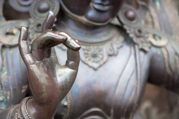 Detail of Buddha statue with Karana mudra hand position stock photo