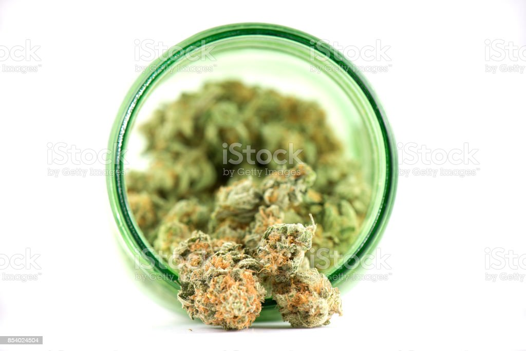 Detail of cannabis buds (mango puff strain) on green glass jar isolated on white stock photo