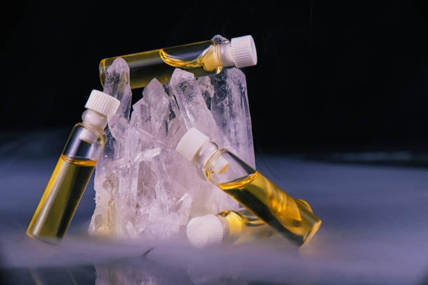 detail der cannabis-öl-behälter und bergkristall isoliert auf schwarz - wachsblume stock-fotos und bilder