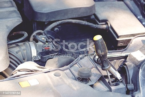 istock detail of Car engine with screwdriver background close up 1147226154