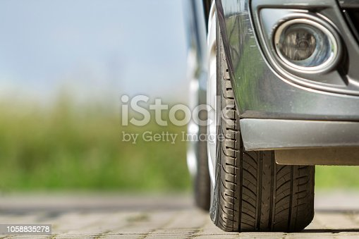 istock Detail of car, wheels with aluminum discs and new black rubber tire protector on light blurred background. Transportation, safety, reliability, modern design concept. 1058835278