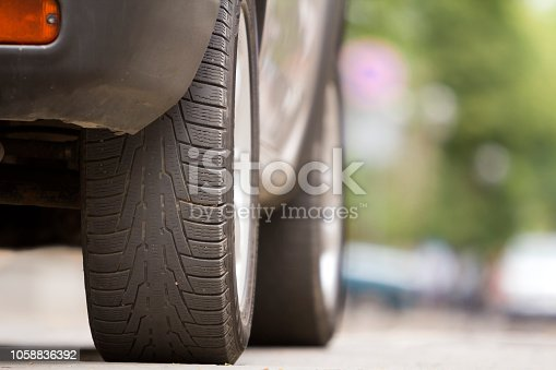 istock Detail of car, wheels with aluminum discs and new black rubber tire protector on light blurred background. Transportation, safety, reliability, modern design concept. 1058836392
