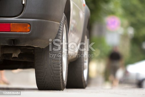 istock Detail of car, wheels with aluminum discs and new black rubber tire protector on light blurred background. Transportation, safety, reliability, modern design concept. 1058836484