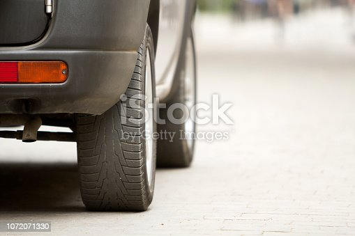 istock Detail of car, wheels with aluminum discs and new black rubber tire protector on light blurred background. Transportation, safety, reliability, modern design concept. 1072071330
