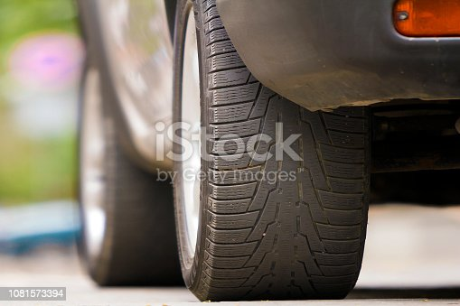 istock Detail of car, wheels with aluminum discs and new black rubber tire protector on light blurred background. Transportation, safety, reliability, modern design concept. 1081573394