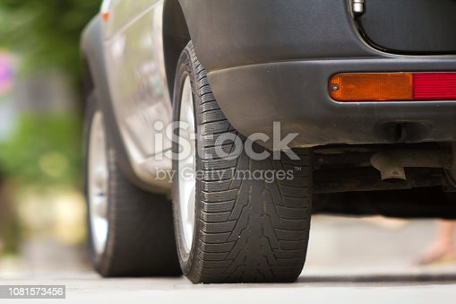 istock Detail of car, wheels with aluminum discs and new black rubber tire protector on light blurred background. Transportation, safety, reliability, modern design concept. 1081573456