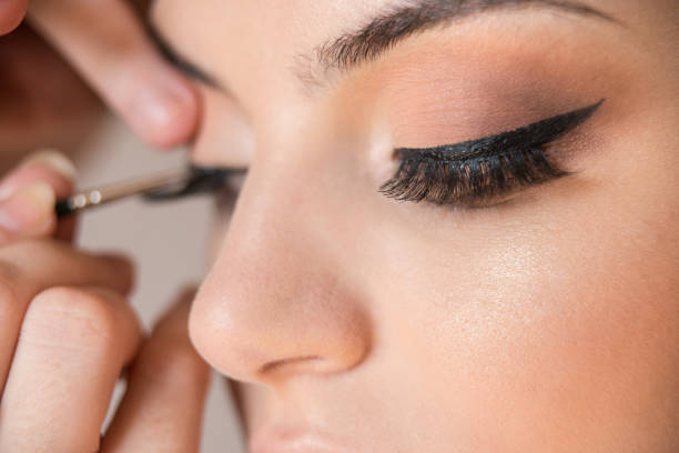 Detail of caucasian model false eyelashes during make-up session. The make-up artist is applying a black eyeliner with the brush Macro detail of caucasian model false eyelashes during make-up session. The make-up artist is applying a black eyeliner with the brush. The model has white, clean complexion. false eyelash stock pictures, royalty-free photos & images