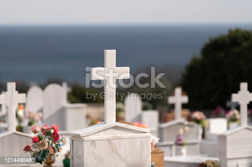 Detail of a Greek Orthodox cemetery on the Greek Island of Chios in the Aegean Sea (seen in the background) at midday in early spring. Shallow depth of field. Blurred background.