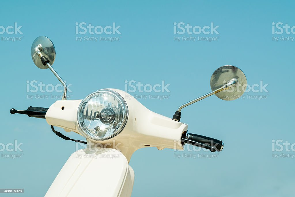 Detail of classic scooter with headlamp and handlebar against sk stock photo