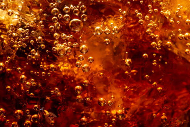 detail van koude sprankelende koolzuurhoudende frisdrank met ijs - cola stockfoto's en -beelden