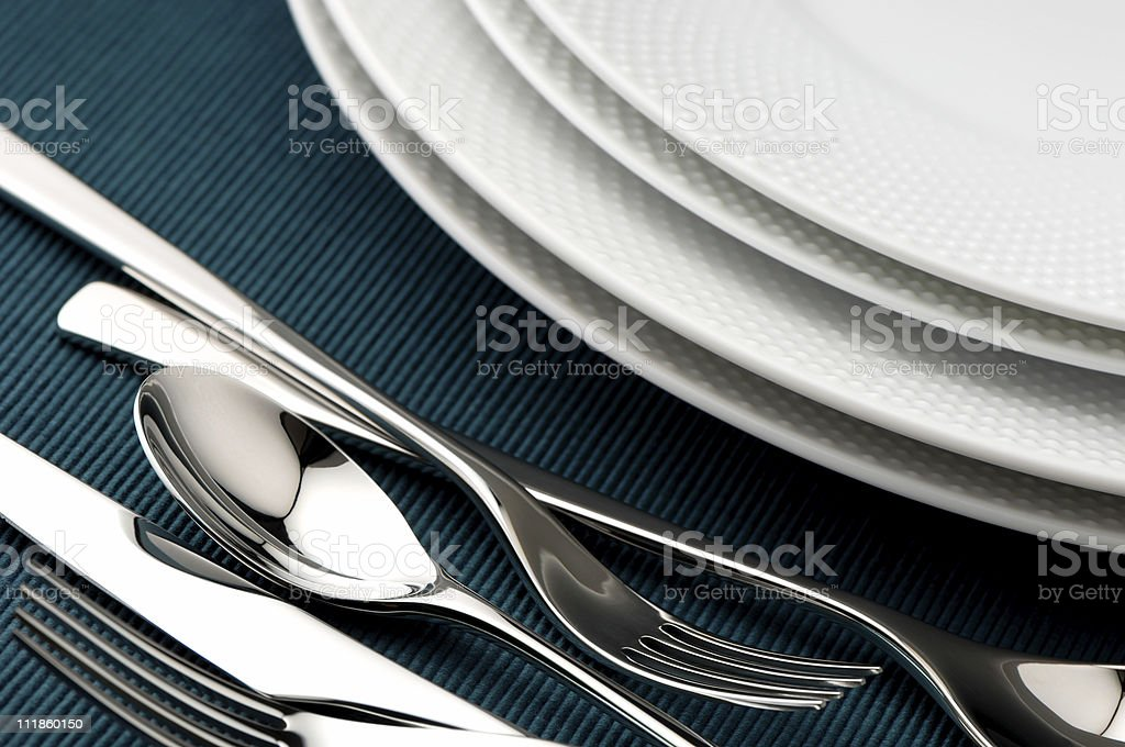 Detail of Designer Blue Table Setting with Chrome Silverware royalty-free stock photo