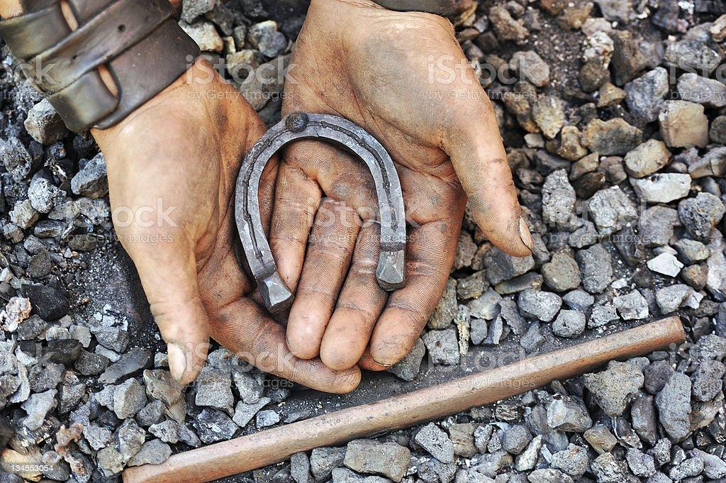 Detail of dirty hand holding horseshoe - blacksmith royalty-free stock photo