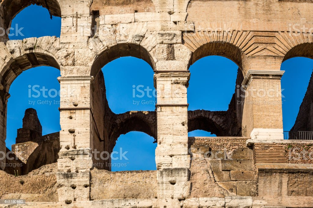 Detail of exterior arched openings / windows at the colosseum in Rome Italy, blue sky background. royalty-free stock photo