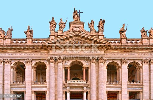 Detail of facade of San Giovanni in Laterano church with Statues of Christ and some saints on the top against blue sky.  Saint John Lateran Basilica Rome, Italy