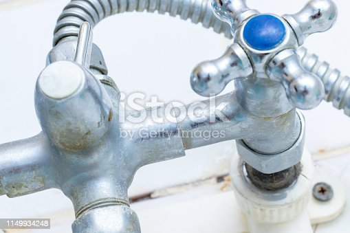Detail of faucet with limescale or lime scale on it, dirty calcified and rusty shower mixer tap, close up.