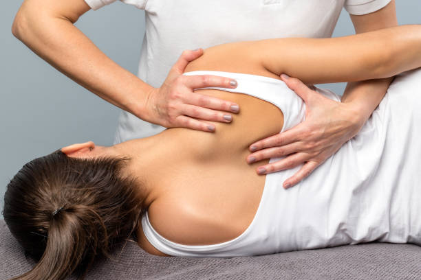 Detail of female therapist manipulating shoulder blade on patient. stock photo