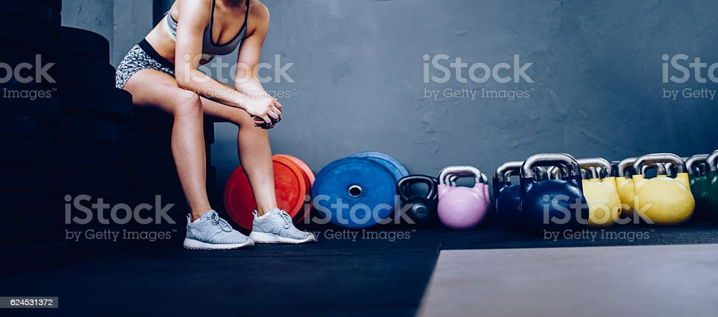 Detail of Girl resting sitting on weights in Gym after stock photo