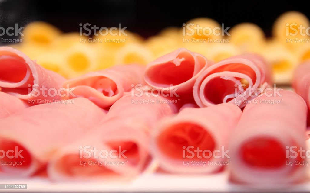 detail of ham in rolls with cheese out of focus in the background