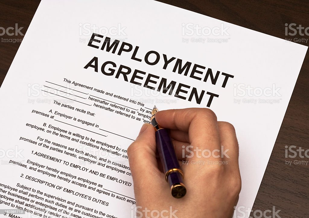 Detail of hand holding pen over employment agreement female hands filling out employment agreement contract Agreement Stock Photo