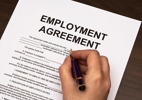 Detail Of Hand Holding Pen Over Employment Agreement Stock Photo - Download Image Now