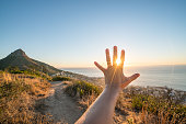istock Detail of hand stretched out to cup rays of sunset 683208962