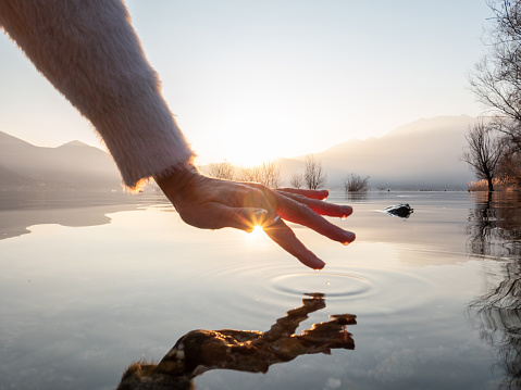 Detail of hand touching and caressing water surface of beautiful lake at sunset, mountain view. Purity freshness clean concept, one person touching lake with hand