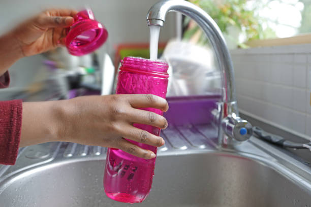 detail of hands filling water bottle at a sink - riempire foto e immagini stock