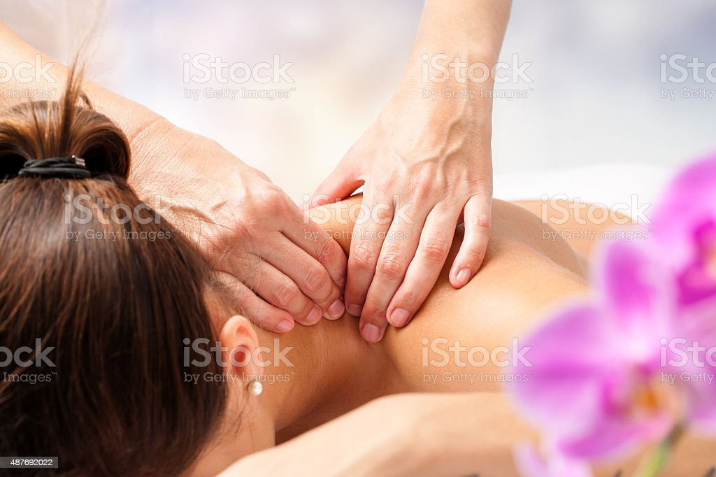 Detail of hands massaging female neck. stock photo