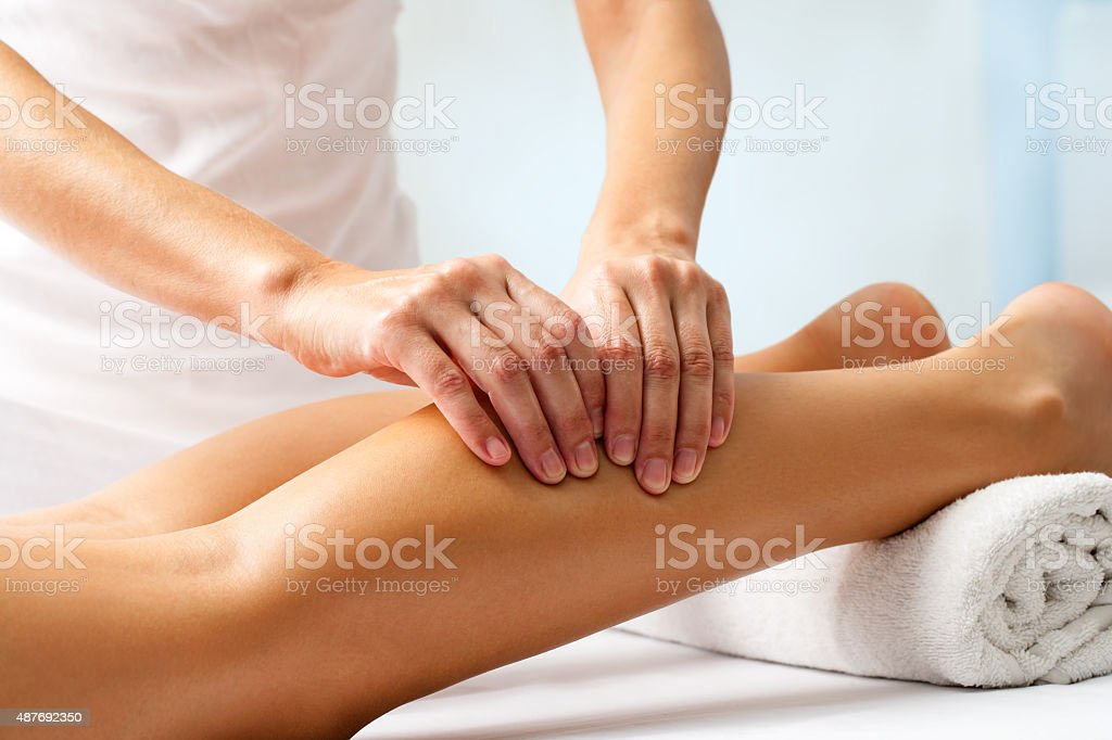Detail of hands massaging human calf muscle. stock photo