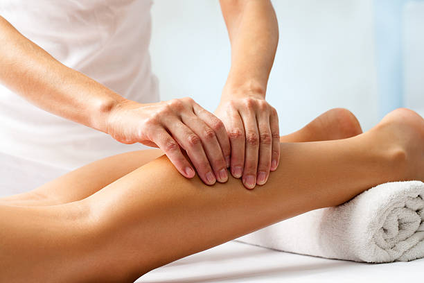 Detail of hands massaging human calf muscle. stock photo