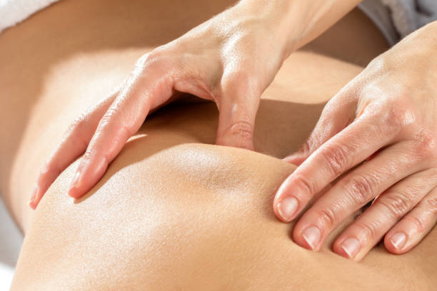 detail of hands massaging shoulder blade. - osteopathy stock pictures, royalty-free photos & images