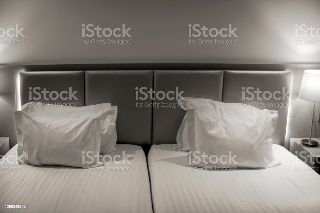 Detail of headboard and white pillows in a bedroom. Bedding, bedside...