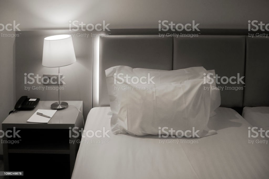 Detail of headboard and white pillow in a bedroom. Bedding, bedside...