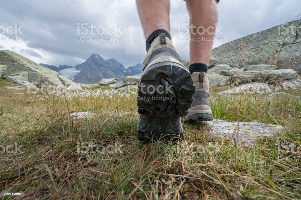 Detail of hiker on trail, view on hiking boots stock photo