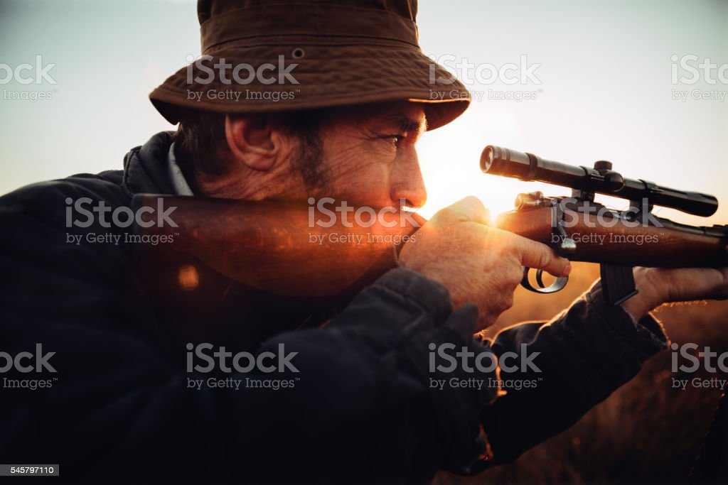 Detail of Hunter looking trough his sniper aiming on prey stock photo