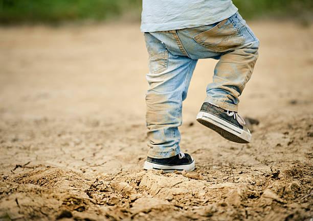 Detalhe de meninos pequenos pernas na lama - foto de acervo