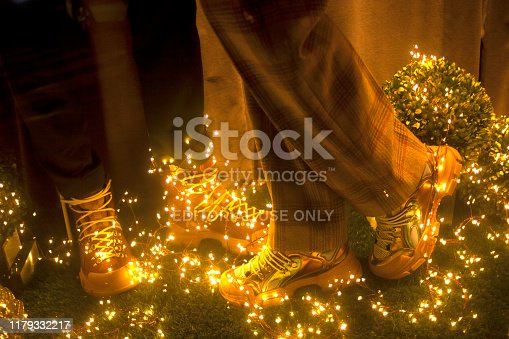 A Coruña, Spain-December 17, 2018: Small part of  store window seen from the street. Detail of mannequin legs wearing  hiking boots , Christmas decorations, gold colored  LED lights . A Coruña, Galicia, Spain.