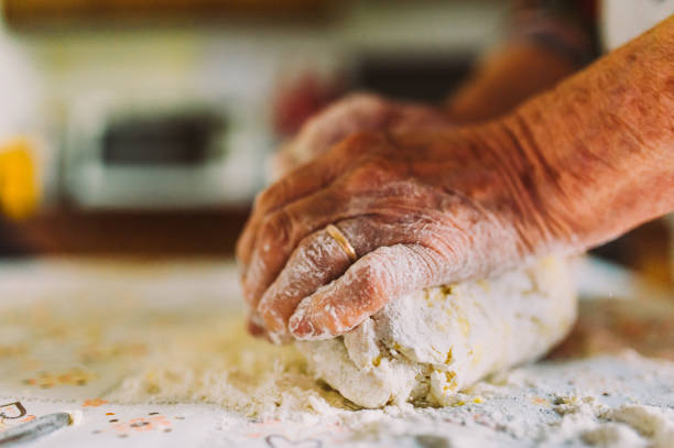 detail of old italian lady's hands making freh raw home made italian pasta in kitchen the old traditional way stock photo