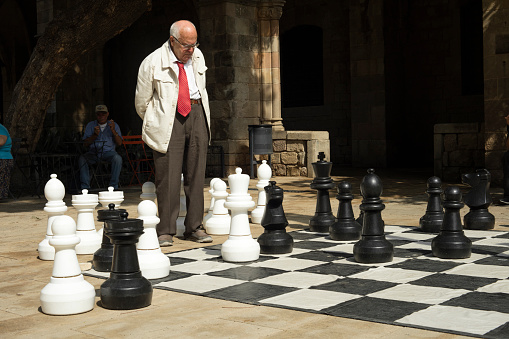 Detail of old man playing gigantic chess outdoors on a sunny day in Barcelona