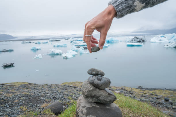 Detail of person stacking rocks by the glacier lagoon in Iceland stock photo