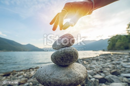Detail of person stacking rocks by the lake, shot in Ticino Canton, Switzerland. People life balance concept