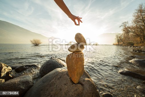 Detail of person stacking rocks by the lake. Sunset time, sunbeam.
