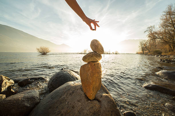 detail of person stacking rocks by the lake - holistic medicine stock photos and pictures