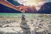 Detail of person stacking rocks by the lake, shot in Alto Adige, Italy.