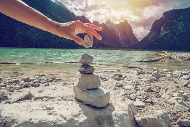 Detail of person stacking rocks by the lake stock photo